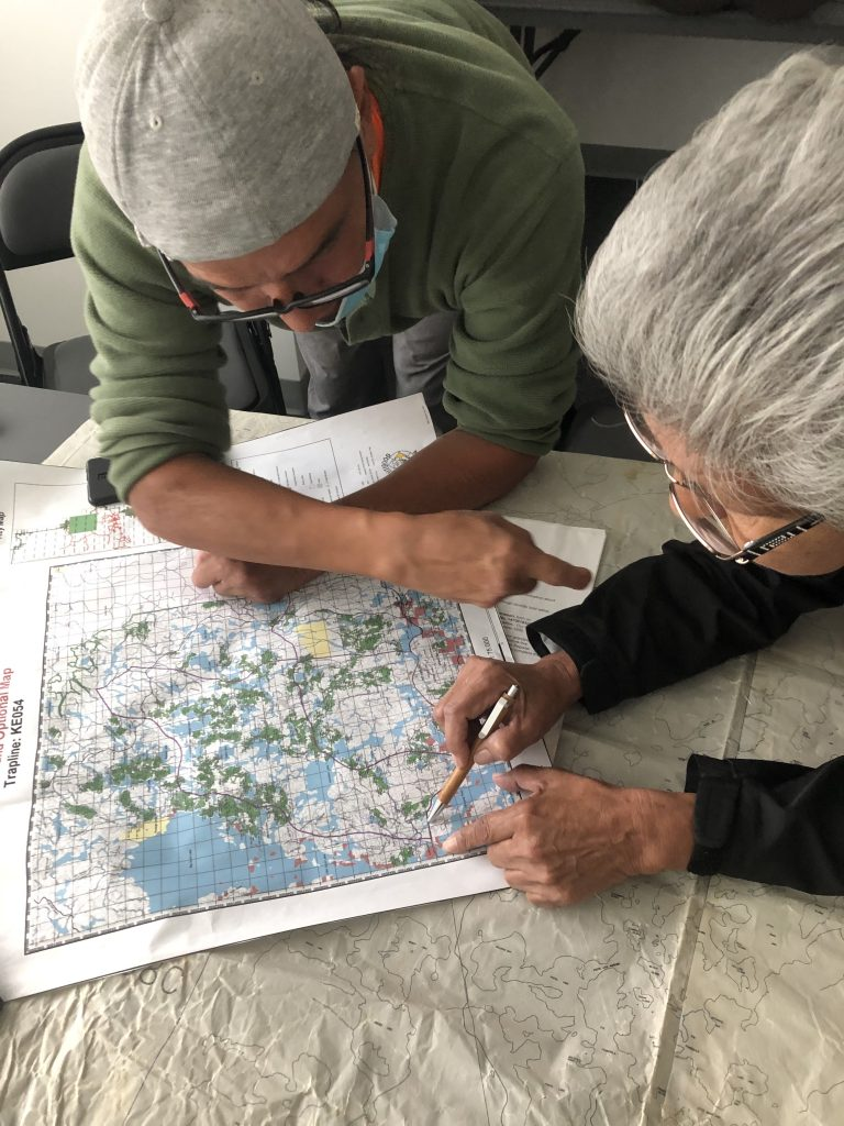 Community members look over a map of the traditional lands of the Niiwin Wendaanimok (Four Winds) Partnership.