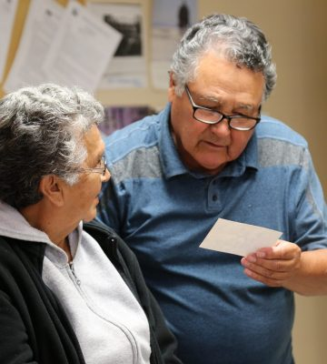 Two elders look at a photo.