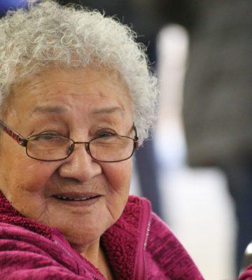 A smiling female elder wearing glasses.