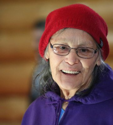 A smiling elder wearing glasses, a red hat and a purple sweater.