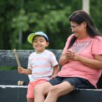 A boy and his mother smiling on a bench. The boy is holding a stick