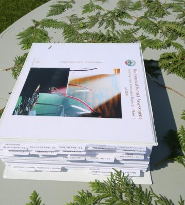 A large binder sit on a table. There is more than 500 pages in the binder.
