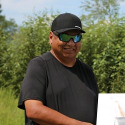 Chief Vernon Redsky holds the Harmonized Impact Assessment report (a large binder) at the HIA ceremony in Shoal Lake 40 First Nation, July 2020.
