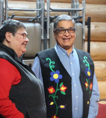 Chief Marilyn Sinclair and Grand Chief Francis Kavanaugh smiling in the roudhouse.