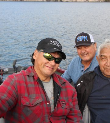 A group of smiling men in a boat.