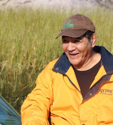 A smiling elder in a boat, he's wearing a hat and a bright yellow jacket.