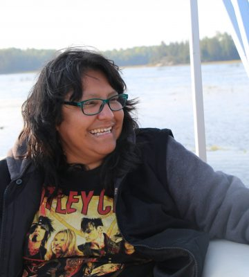 A woman smiles on a boat.